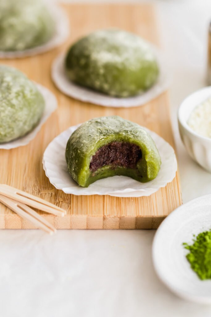 Bitten matcha mochi on cupcake liners on wooden board, revealing red bean paste inside, toothpicks in foreground, more mochi in the background.