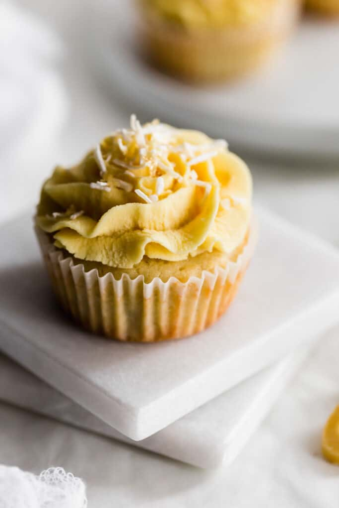 Close up of coconut cupcake with yellow passionfruit frosting and coconut flakes on two square marble trivets.