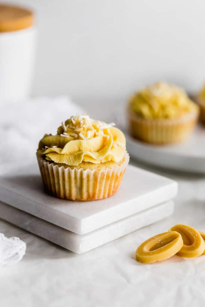 Close up of coconut cupcake and passionfruit frosting with coconut flakes, yellow chocolate callets in the foreground.