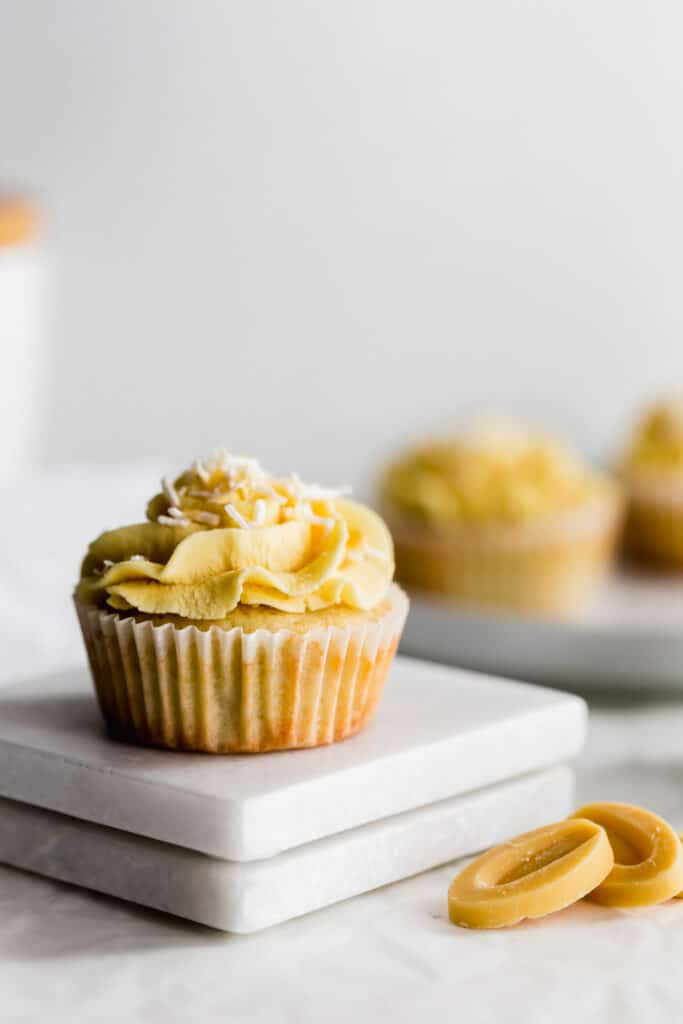 Close up of coconut cupcake with yellow passionfruit and coconut flakes, yellow chocolate callets in foreground, more cupcakes in the background.