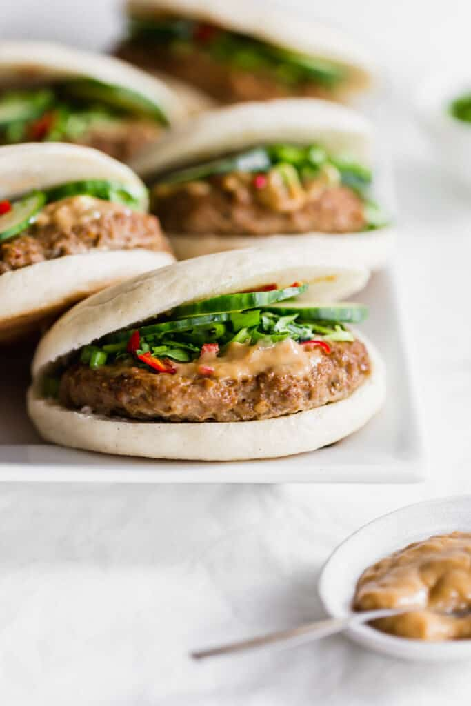 A close up of cumin turkey burgers on a white rectangular plate with tahini sauce on the side.