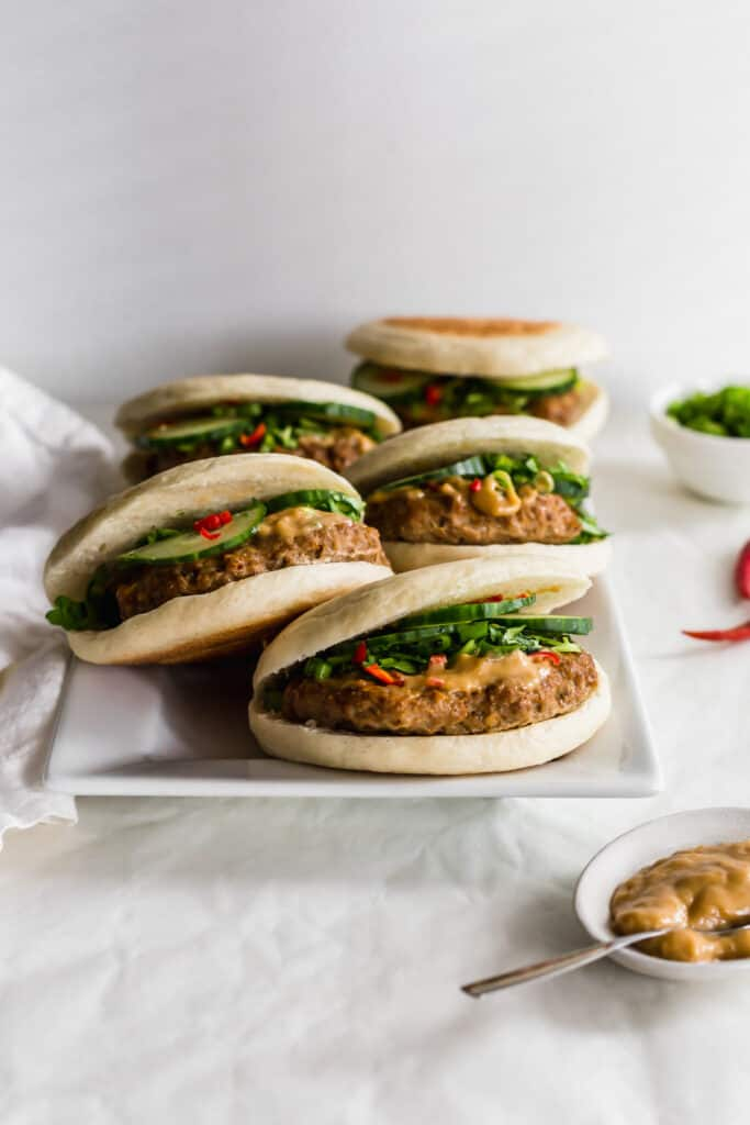A group of cumin turkey burgers on a white rectangular plate with tahini sauce on the side.