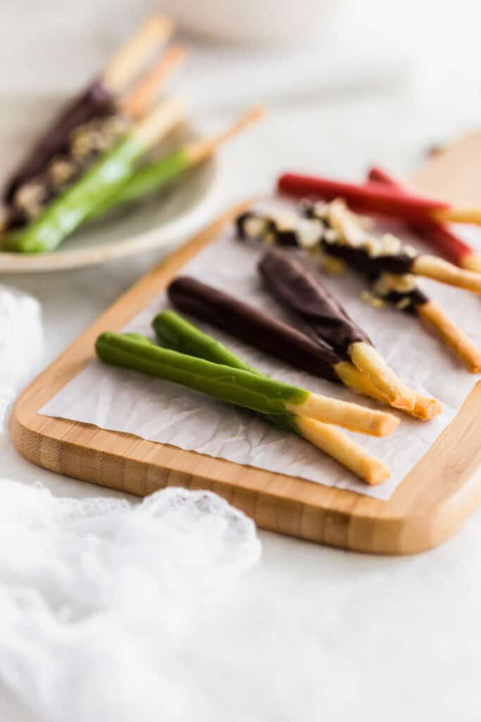 Close up of matcha and chocolate pocky sticks lying on a wooden board.