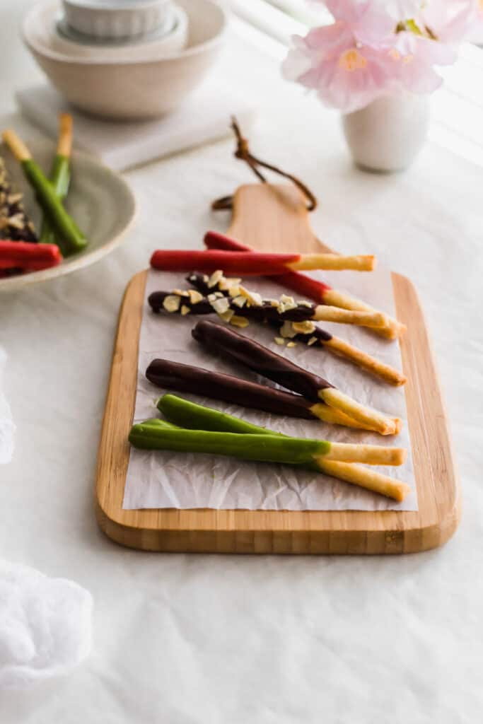 Various chocolate-dipped pocky sticks on a wooden board.