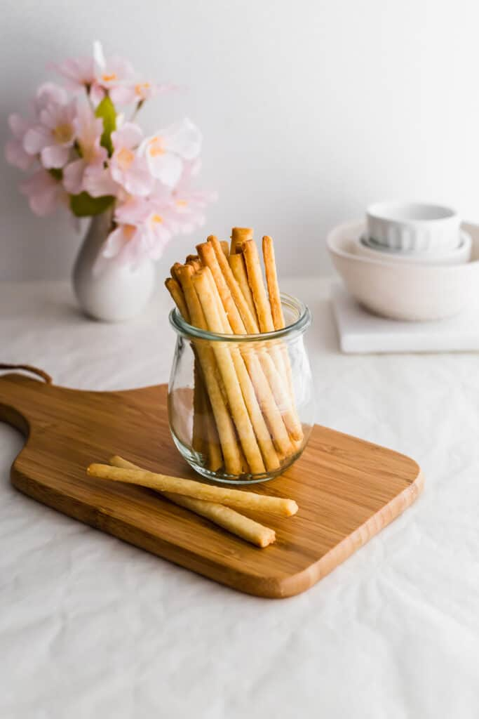 A jar of un-coated biscuit sticks on a wooden board with sticks lying on the board.