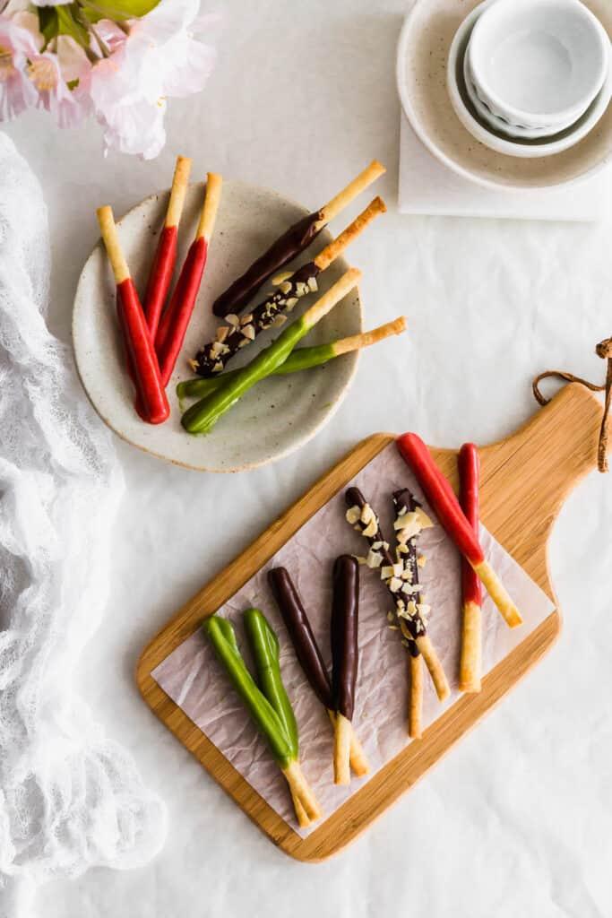 Various chocolate-dipped pocky sticks on a wooden board and pocky sticks on a small plate.
