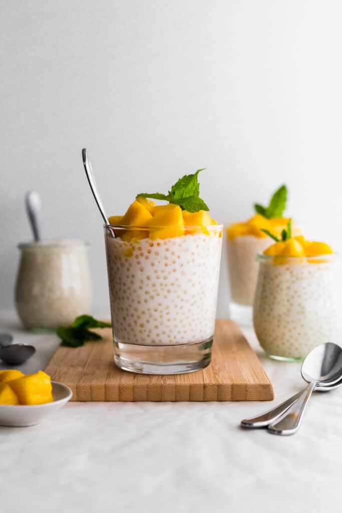 Glass of mango sago pudding with spoon on wooden board.