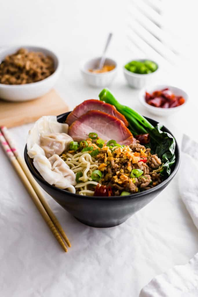 Close up of Kolo Mee in a black bowl with chopsticks and toppings in background.