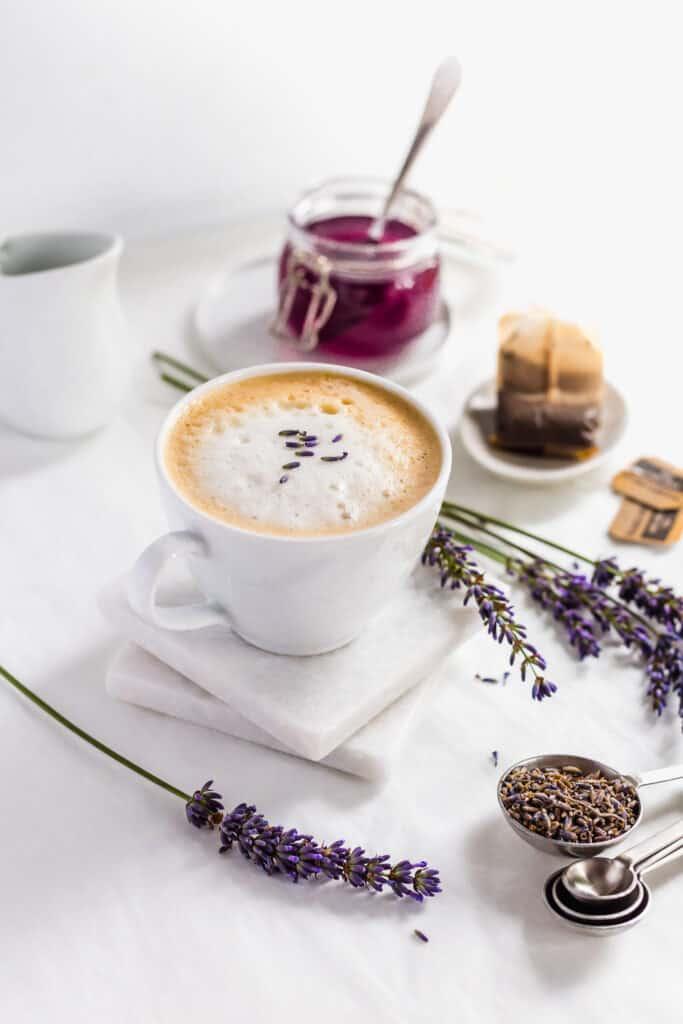 Mug of lavender earl grey tea latte on white marble coasters with lavender flowers.