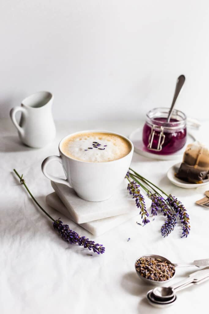 Mug of lavender earl grey tea latte on white marble coasters with lavender flowers.