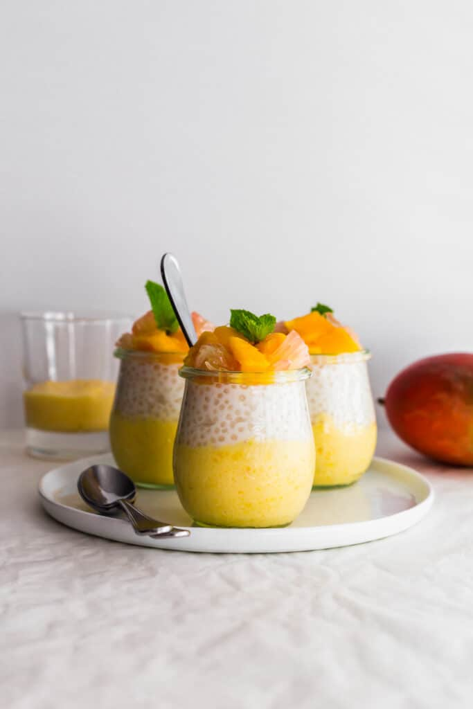 Jars of mango pomelo sago on white plate with spoons on the side.