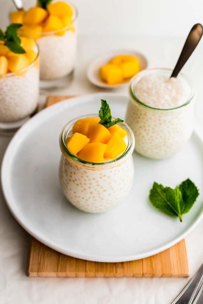 Jar of mango sago on white round plate on wooden board, jar of sago with spoon in background.