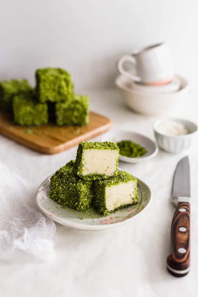 A cut cross section of matcha lamington on a small plate with knife on side, lamingtons on wooden board in background.