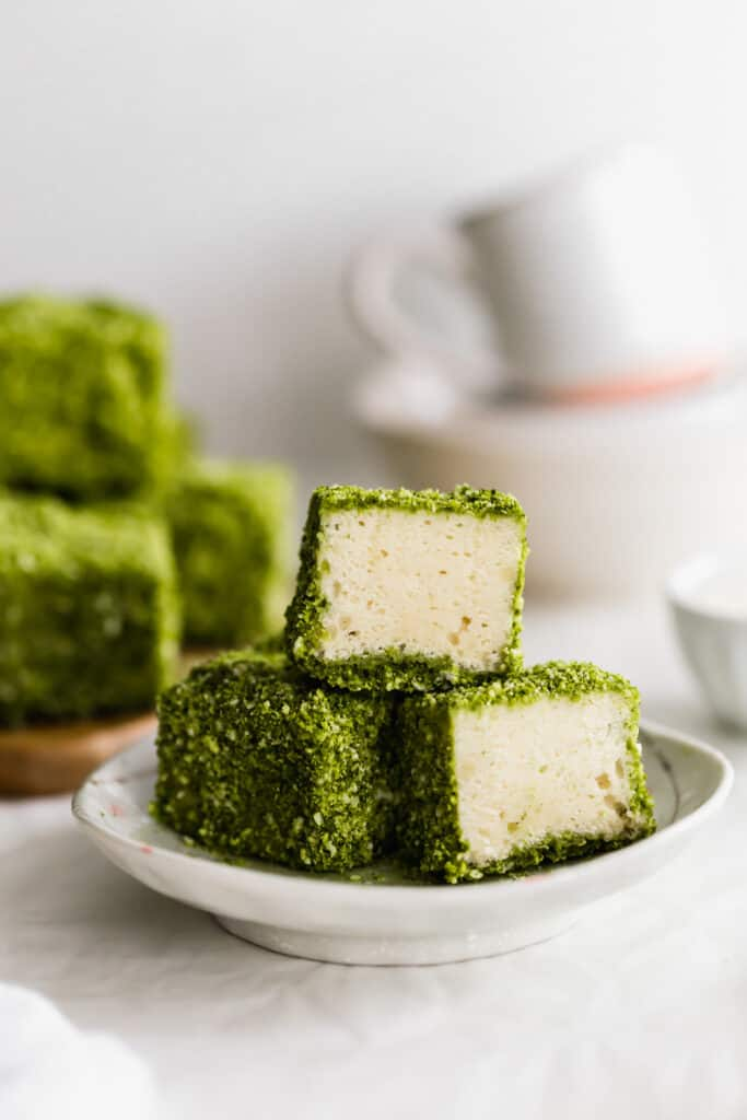 A close up of a stack of three green matcha lamingtons on a small plate, lamingtons in background.