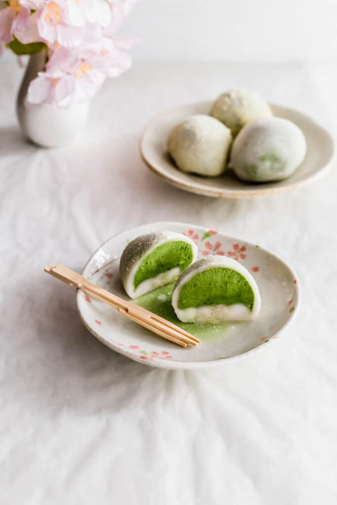 A cut white mochi revealing green matcha ice cream on a small plate with two toothpicks, a small plate of whole mochi in the background.