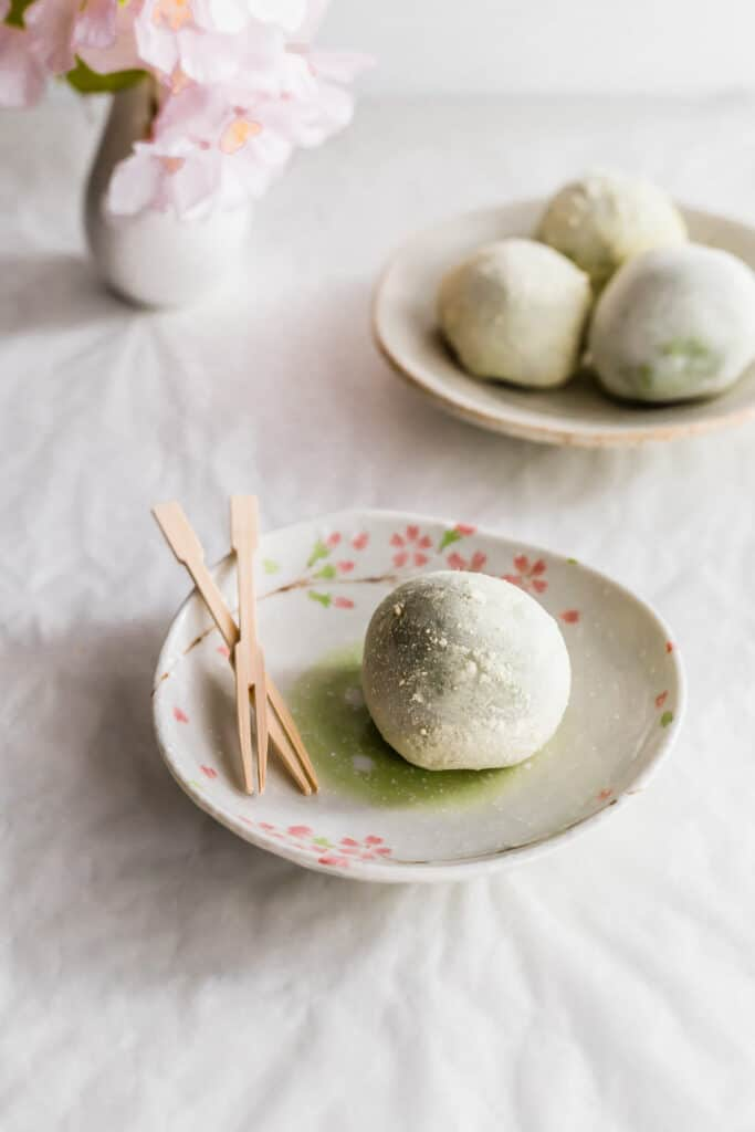A white mochi on a small plate with two toothpicks, a small plate of whole mochi in the background.