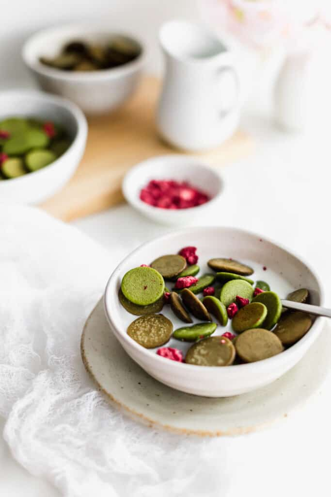 A spoonful of mini hojicha and matcha pancakes with dried raspberries in milk in a bowl on a small plate, jug of milk, raspberries and mini pancakes in background.