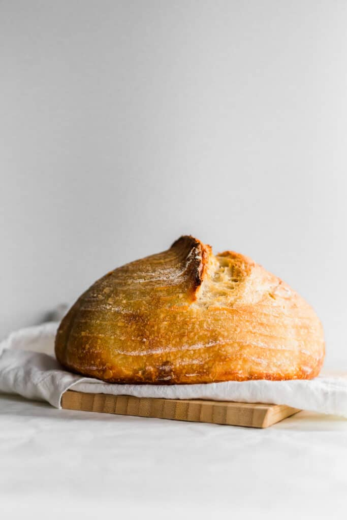 A baked sourdough bread loaf on white linen on top of wooden board.