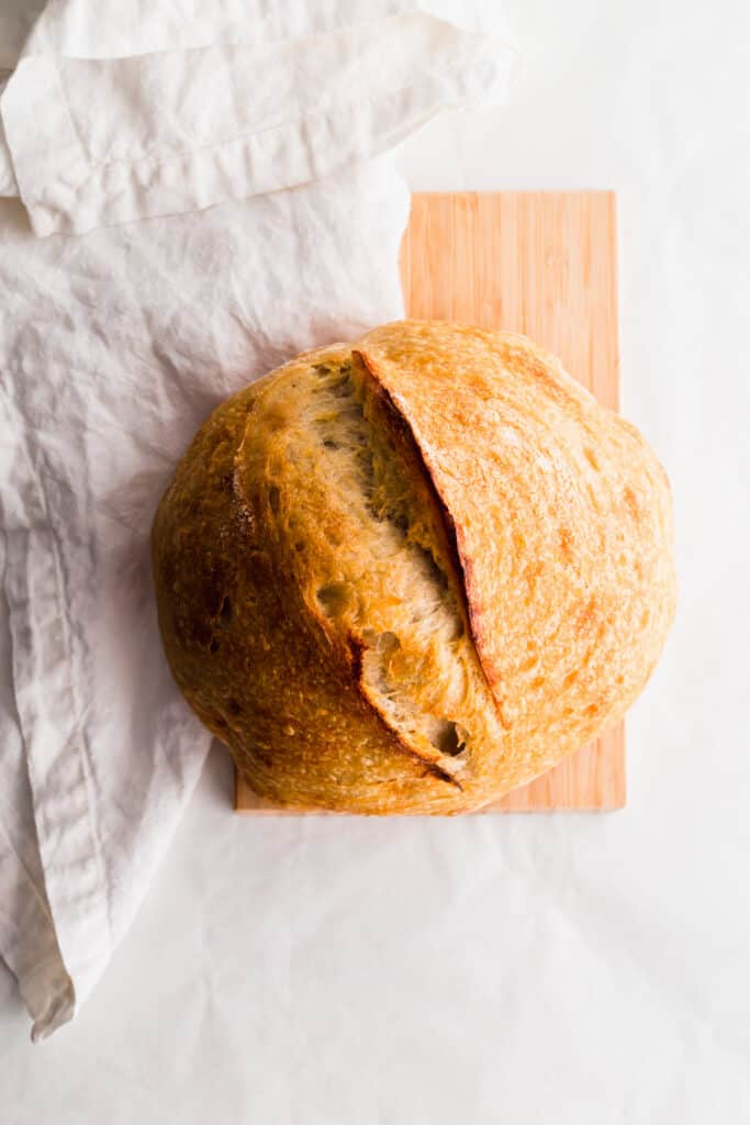 A baked sourdough bread loaf on wooden board with white linen on side.