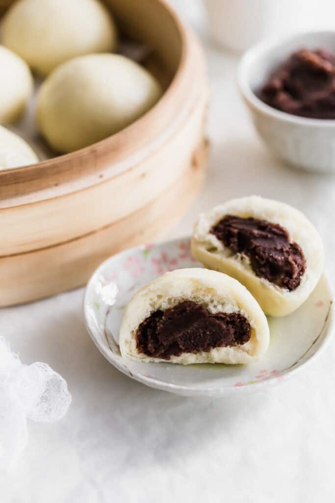 A close up of torn steamed bun revealing red bean paste filling on small plate, with whole buns in a round bamboo basket and red bean paste in background.