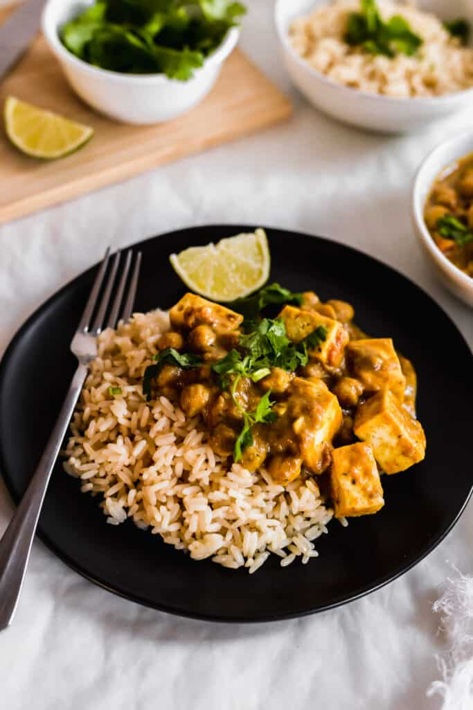 Rice with chana dal and tofu on a black plate with fork.