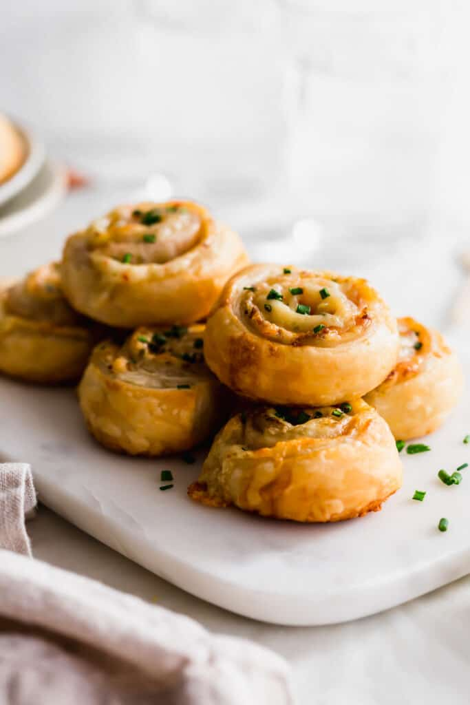 A stack of ham and cheese puff pastry scrolls topped with chives on marble.