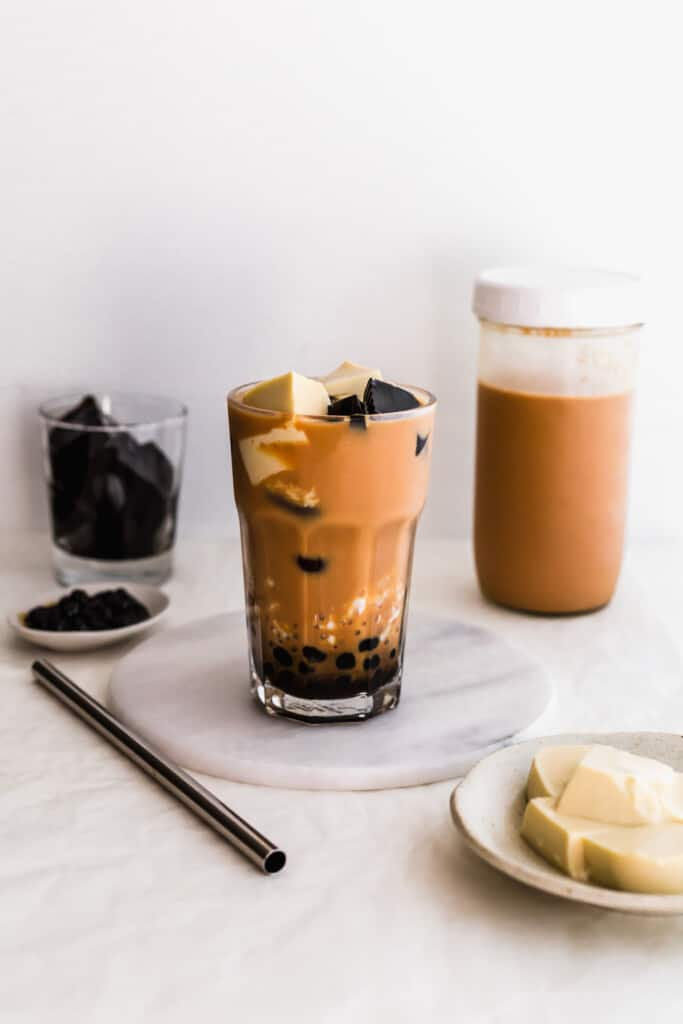 A glass of milk tea with boba, sago, egg pudding, grass jelly on a marble trivet and straw on the side, milk tea and grass jelly in the background.