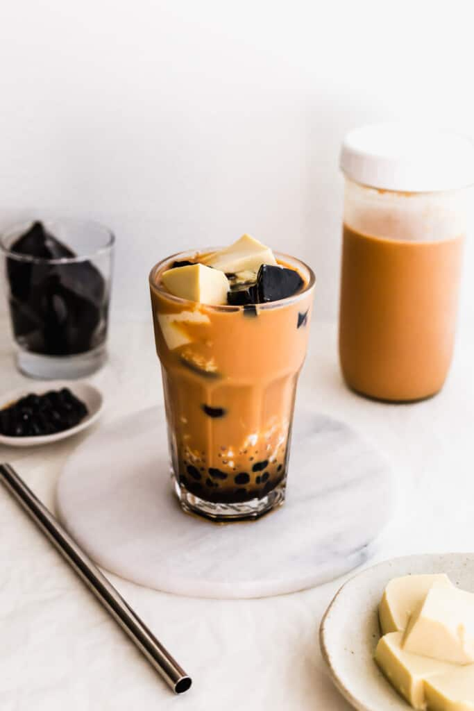 A glass of milk tea with boba, sago, egg pudding, grass jelly on a marble trivet and straw on the side.