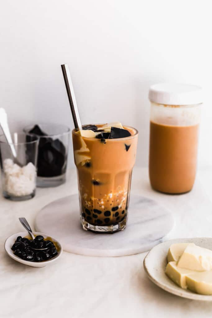 A glass of milk tea with boba, sago, egg pudding, grass jelly on a marble trivet and straw on the side, sago, milk tea and grass jelly in the background.