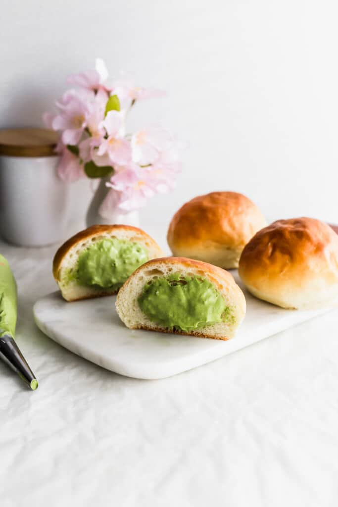 Cut bun exposing matcha cream with whole buns in the background.