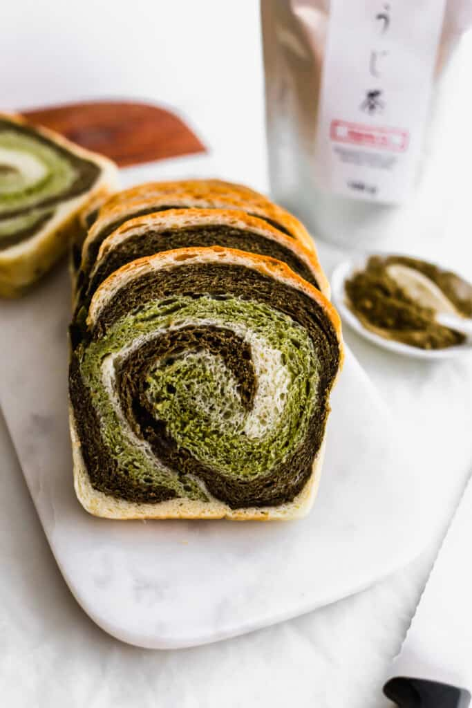Slices of hojicha matcha swirl bread on marble with bread knife, hojicha powder and tea packaging in the background.