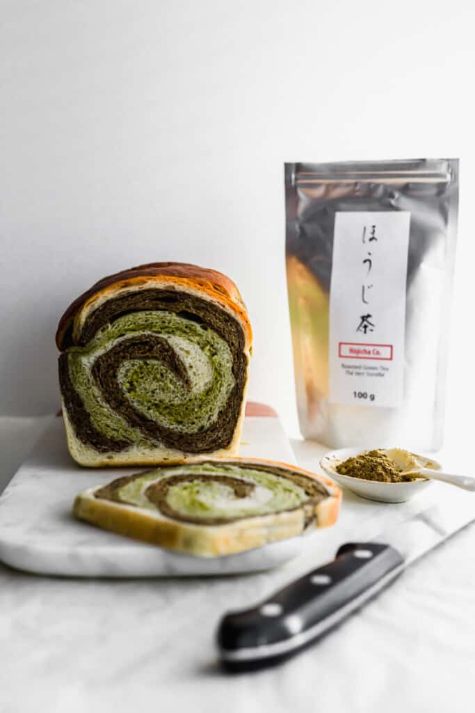 A slice of hojicha matcha swirl bread in foreground on marble and unsliced loaf behind, with bread knife and hojicha powder and tea packaging in the background.