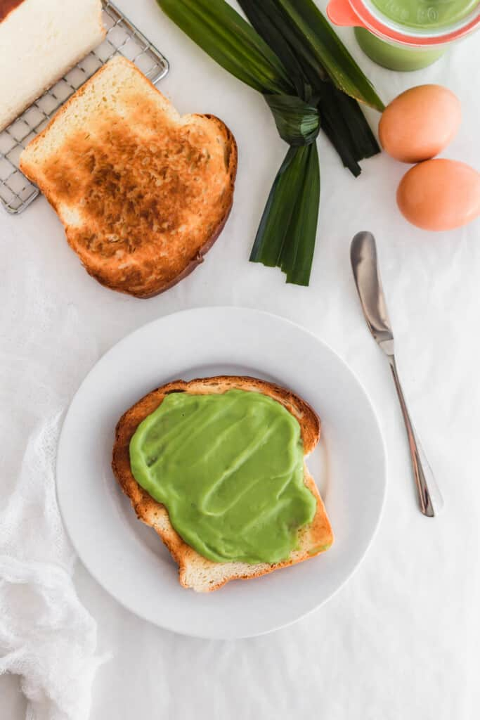 A close up of green kaya pandan coconut jam toast on white round plate, knife, eggs, pandan leaves.