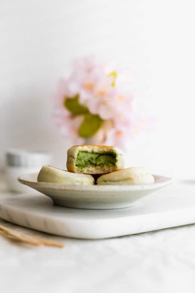 Mini buns on a small plate on marble with a bitten bun revealing green matcha custard.