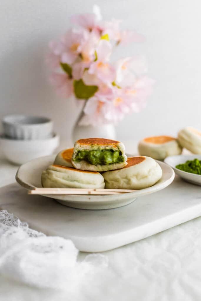 Mini buns on a small plate on marble with an open bun revealing green matcha custard.