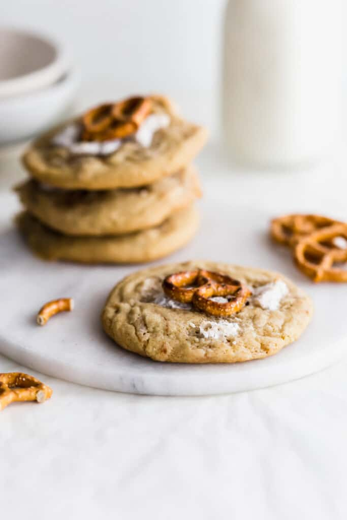 A SunButter marshmallow and pretzel cookie in foreground with three cookies on round marble trivet, with broken pretzel pieces scattered around, jar of milk in the background.