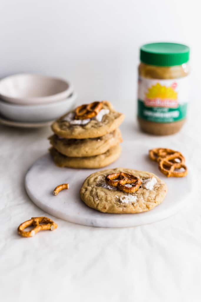 SunButter marshmallow and pretzel cookies with on round marble trivet, with broken pretzel pieces scattered around, bowls and SunButter jar in the background.