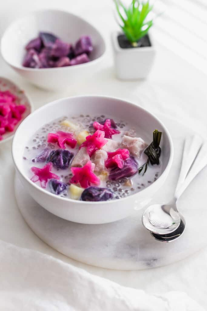 A bowl of pink star jellies, sago, purple yam in coconut soup in a white bowl on marble trivet with 2 spoons, bowl of purple yam in the background.