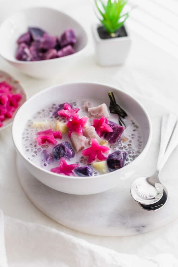Close up of a bowl of burbur cha cha with pink star jellies, purple yam in coconut soup with 2 spoons on the side, bowl of purple yams in the background.