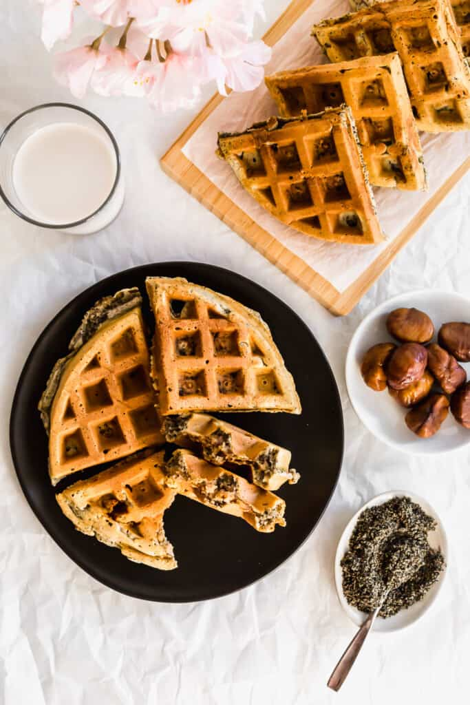 Black sesame waffles on a black plate with chestnuts, black sesame powder, glass of milk and waffles on a wooden board.