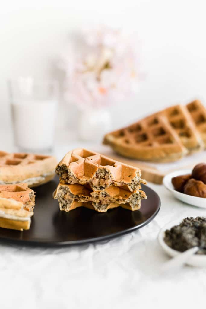 A torn black sesame waffle with chestnut filling stacked on a black plate, glass of milk and waffles in the background.