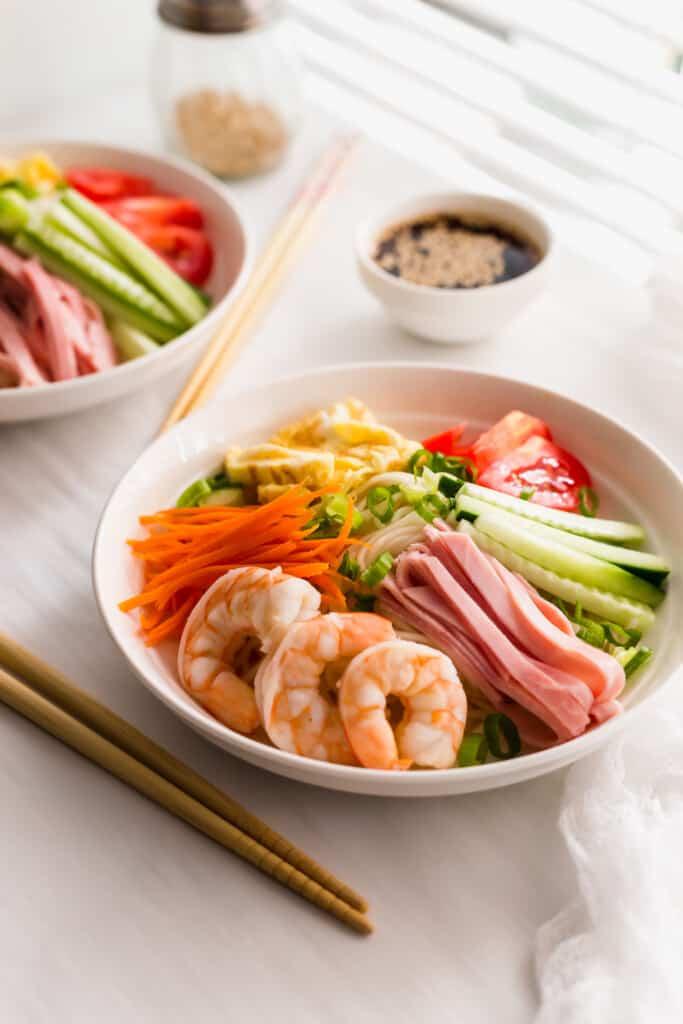 Bowls of Hiyashi Chuka Cold Ramen Noodles with chopsticks on side.