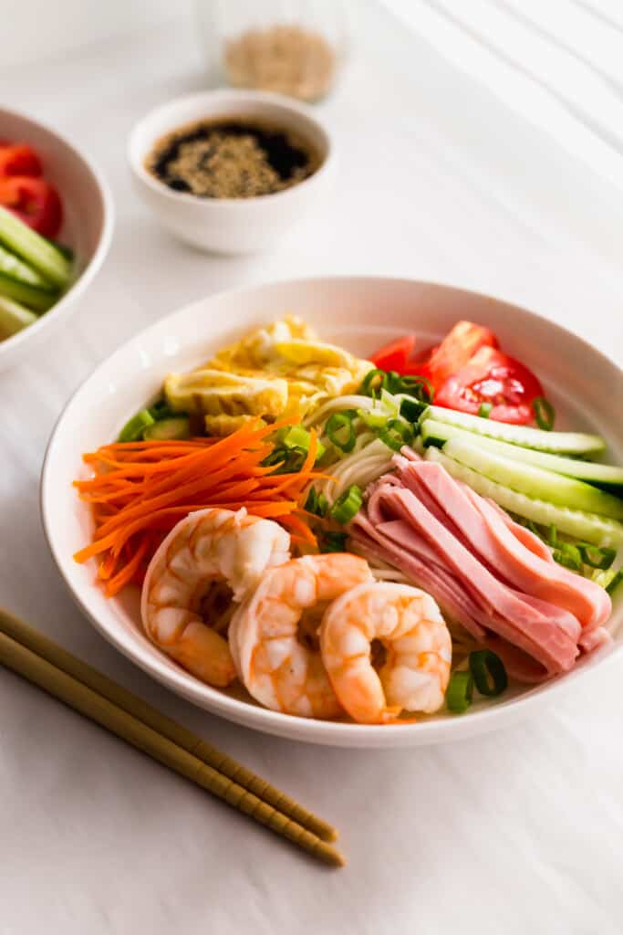 Close up of a bowl of Hiyashi Chuka Cold Ramen Noodles with chopsticks on side.