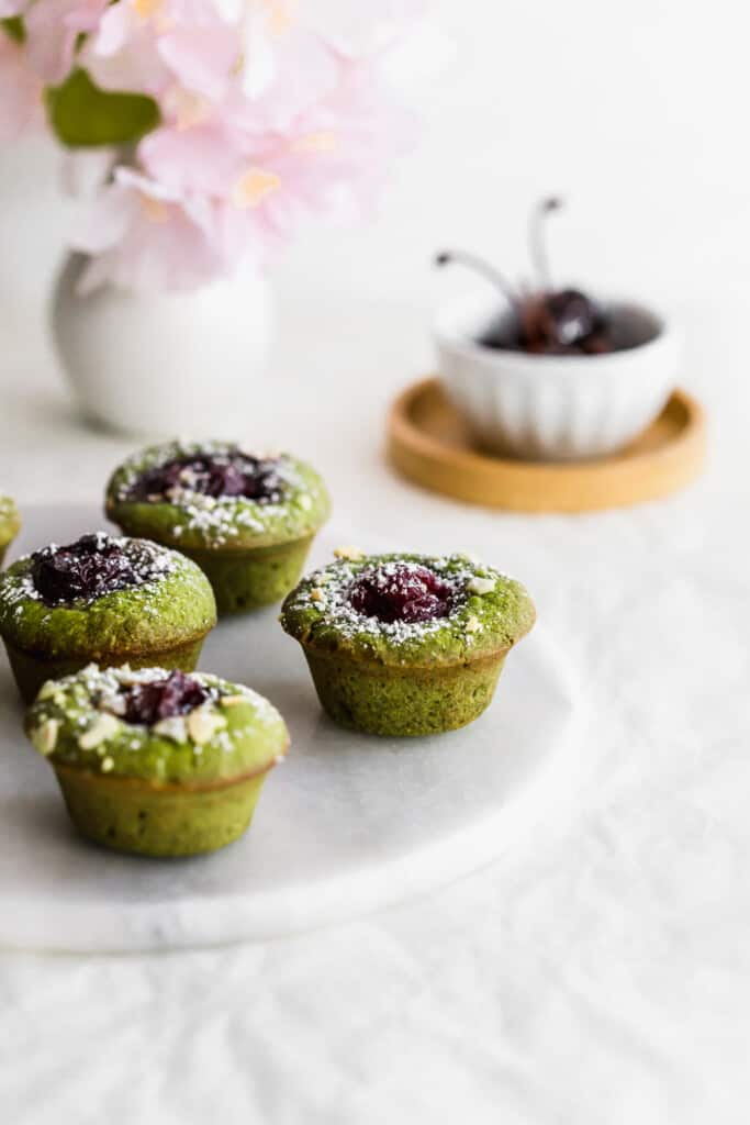 Green matcha and cherry financiers on a round marble trivet with a bowl of cherries in the background.