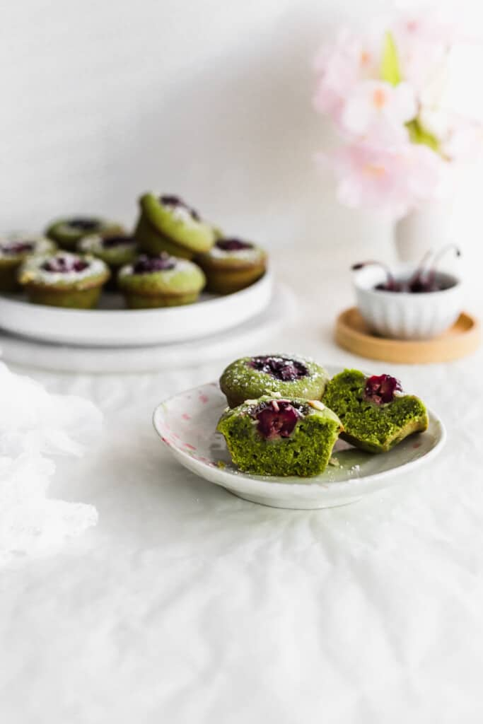 Cut green matcha and cherry financiers on a small plate with more financiers and a bowl of cherries in the background.