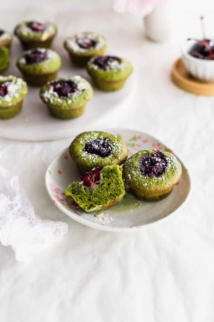 Green matcha and cherry financiers with one cut in half, exposing the inside on a small plate, more financiers in the background. t with a bowl of cherries in the background.
