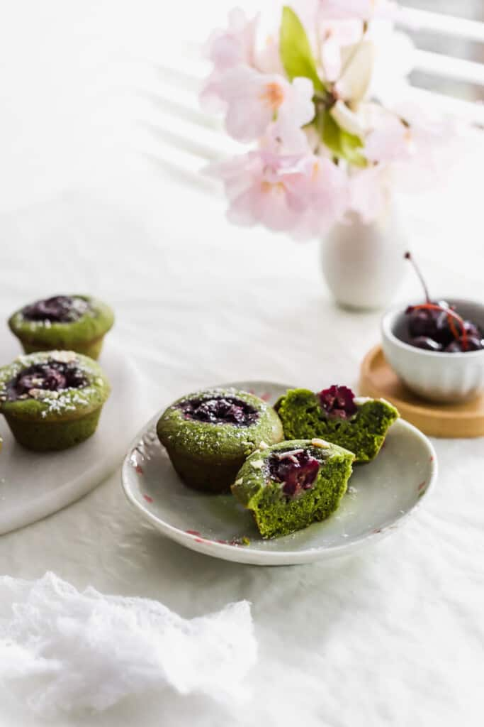 Cut green matcha and cherry financiers on a small plate with whole financiers and a bowl of cherries to the side.