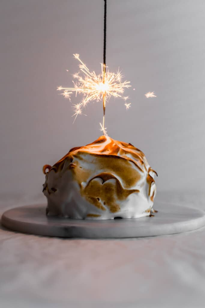 Mini baked Alaska with torched meringue on round marble trivet with lit sparkler in the centre.