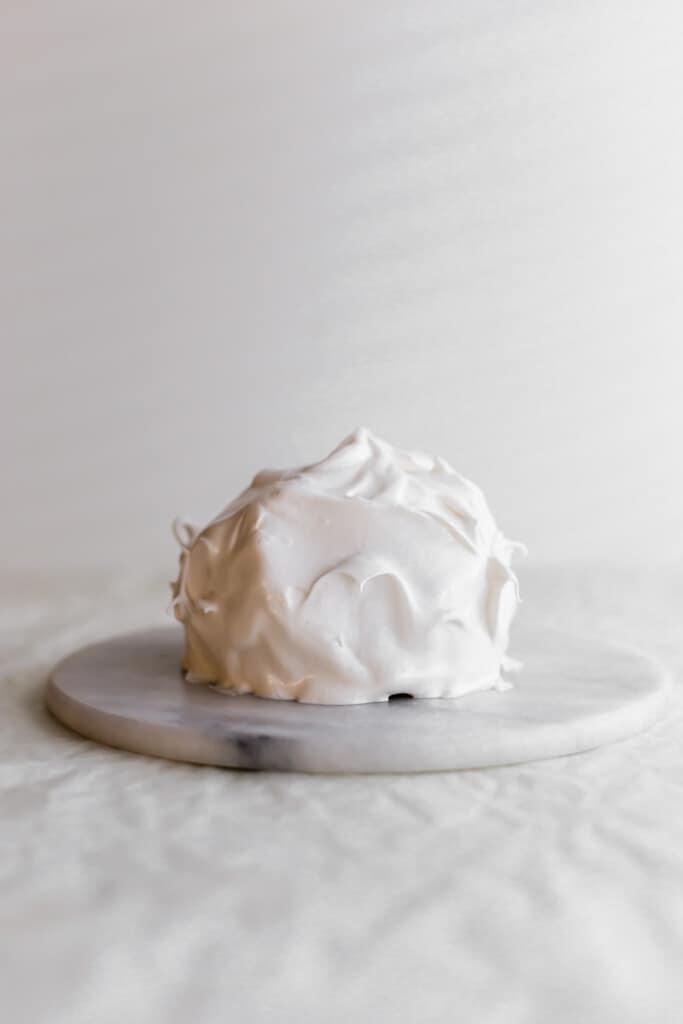 A white meringue-covered mini baked Alaska on white round marble trivet.