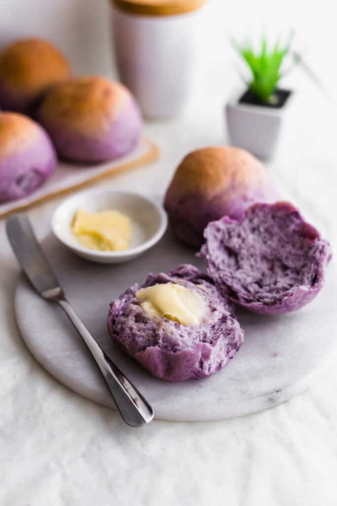A torn open purple sweet potato bun with butter smeared on the surface, on a marble trivet with knife, more buns in the background.